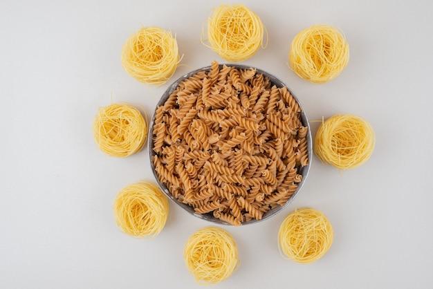 Schüssel mit spiralnudeln und spaghetti-nestern auf weißer oberfläche