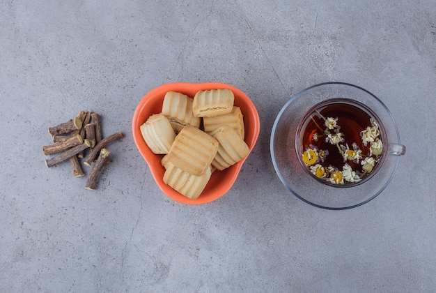 Schüssel mit süßen keksen und einer glasschale mit heißem tee auf steinoberfläche.