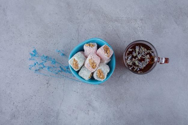 Schüssel mit süßen köstlichkeiten mit walnüssen und tasse heißem tee auf steinhintergrund.