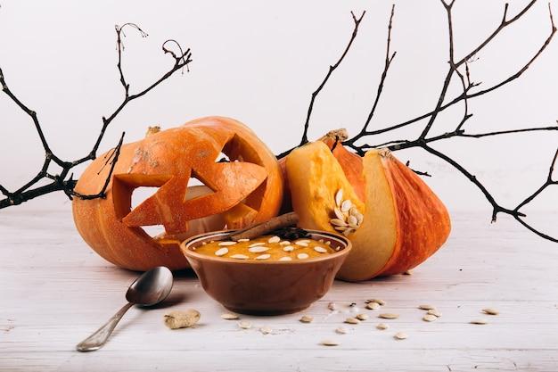 Schüssel mit suppe steht vor scarry halloween-kürbis auf dem tisch