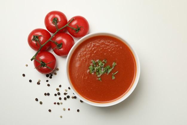 Schüssel mit tomatensuppe und zutaten auf weiß