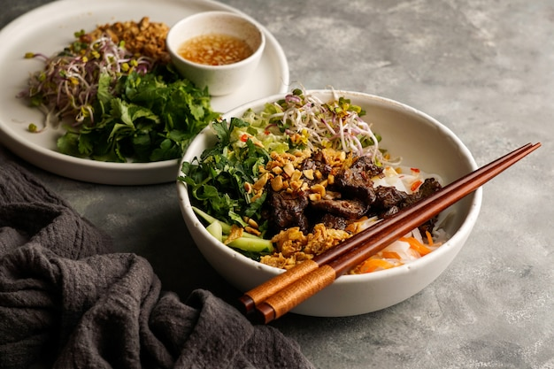 Schüssel mit traditionellem vietnamesischen nudelsalat - bun bo nam bo, mit rindfleisch, reisnudeln, frischen kräutern, eingelegtem gemüse und fischsauce