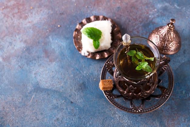 Schüssel mit türkischer zuckerwatte pismaniye und schwarzem tee mit minze auf einer dunklen oberfläche