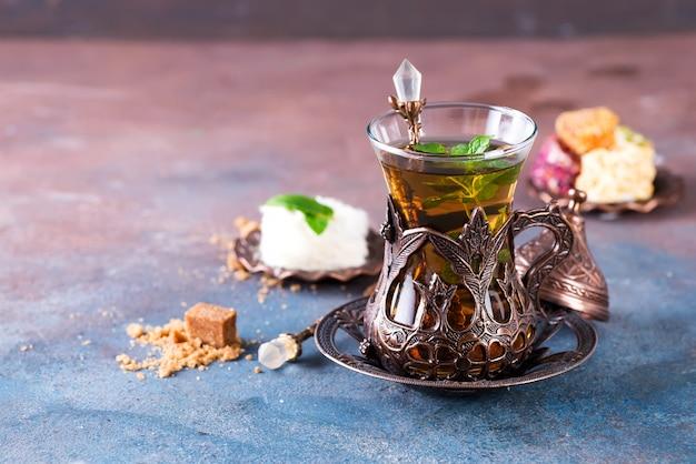 Schüssel mit türkischer zuckerwatte pismaniye und schwarzem tee mit minze