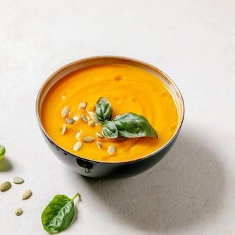 Schüssel mit vegetarischer cremesuppe aus kürbis oder karotte, dekoriert mit frischem basilikum, olivenöl und kürbiskernen auf weißem texturtisch mit zutaten oben. quadratisches bild