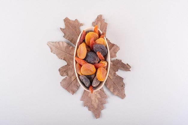 Schüssel mit verschiedenen bio-früchten mit trockenem blatt auf weißem hintergrund. foto in hoher qualität
