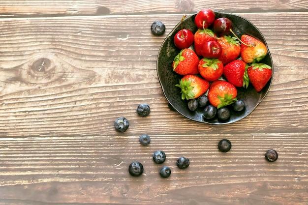 Schüssel mit verschiedenen früchten auf einem holztisch