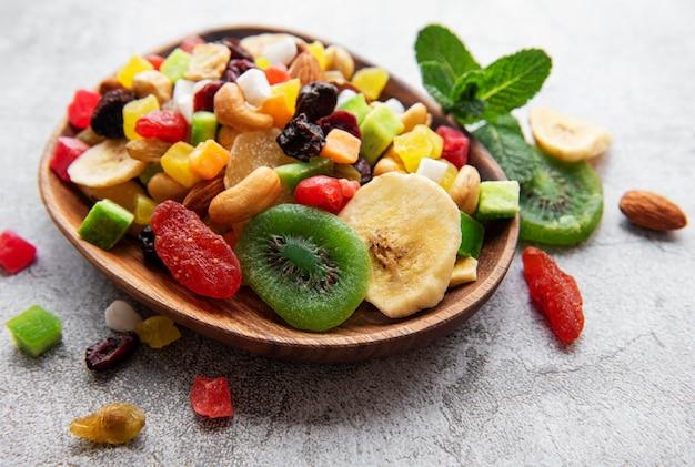 Schüssel mit verschiedenen getrockneten früchten und nüssen auf einer grauen betonoberfläche