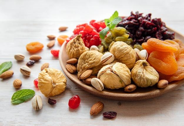 Schüssel mit verschiedenen getrockneten früchten und nüssen auf einer holzoberfläche