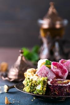 Schüssel mit verschiedenen stücken des türkischen vergnügens lokum und des schwarzen tees mit minze