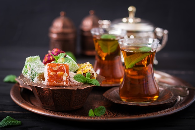 Schüssel mit verschiedenen stücken türkischen genusses lokum und schwarzem tee mit minze auf einem dunklen tisch