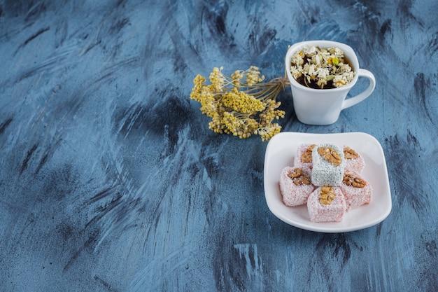Schüssel mit verschiedenen süßen köstlichkeiten mit einer tasse tee auf blau.