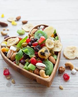 Schüssel mit verschiedenen trockenfrüchten und nüssen auf einer holzoberfläche