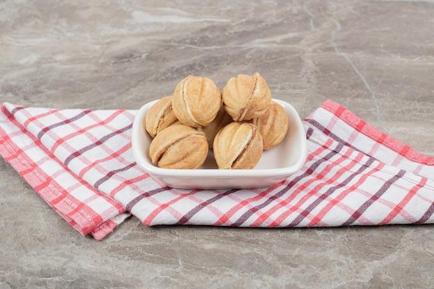 Schüssel mit walnussförmigen keksen auf tischdecke. hochwertiges foto