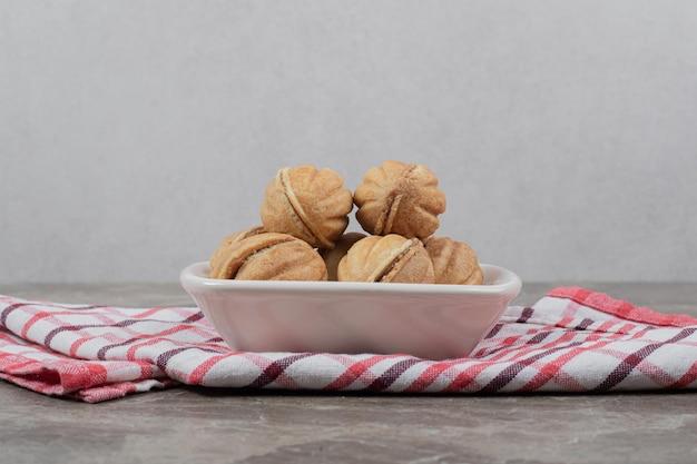 Schüssel mit walnussförmigen keksen auf tischdecke.