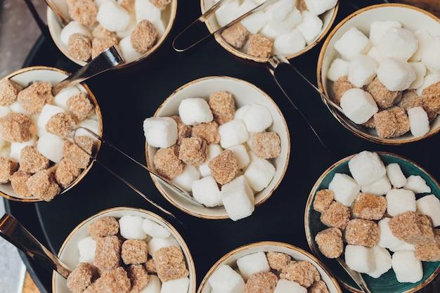 Schüssel mit weißen und braunen zuckerwürfeln und zangen.