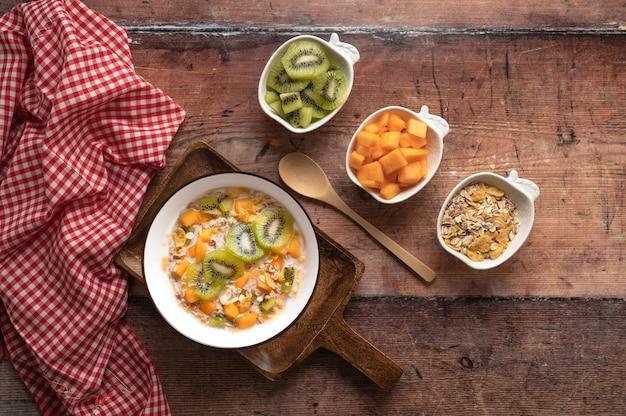 Schüssel müsli mit milch und früchten auf hölzernem hintergrund köstliche gesunde frühstücks-draufsicht
