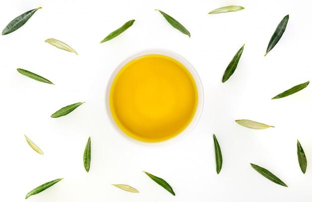 Schüssel natives olivenöl extra mit olivenblättern. zenitalflugzeug