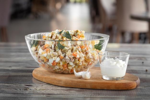 Schüssel olivier traditioneller salat, mischung aus gehacktem gekochtem gemüse und fleisch