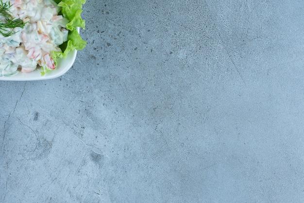 Schüssel oliviersalat mit einem salatblatt auf marmor.