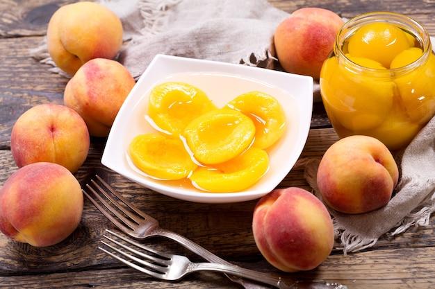 Schüssel pfirsichkonserven mit frischen früchten auf holztisch