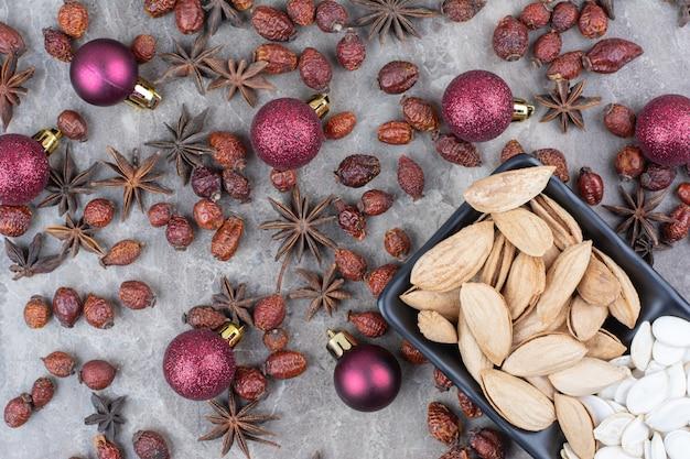 Schüssel pistazien- und kürbiskerne mit hagebutten und weihnachtskugeln.