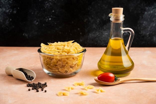 Schüssel rohe nudeln und olivenöl auf orange tisch.