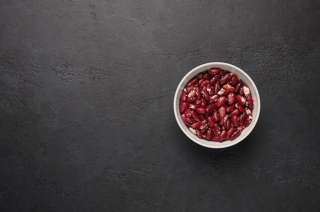 Schüssel rote bohnen auf einer strukturierten hölzernen schwarzen oberflächengemüseprotein-gesunden lebensmitteloberansicht