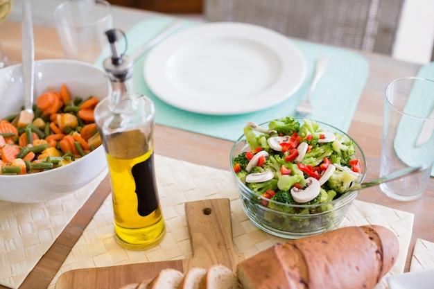 Schüssel salat und olivenöl auf esstisch