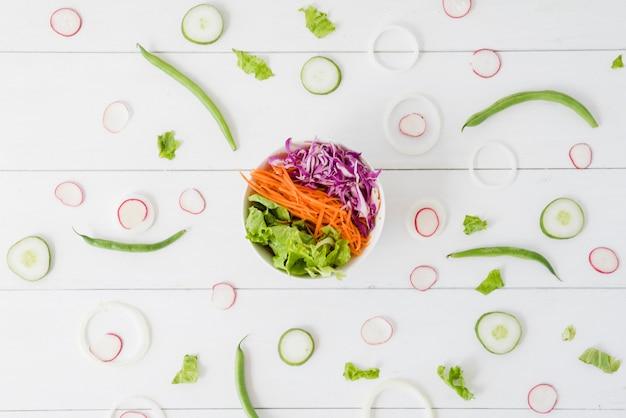 Schüssel salataufstrich mit rübe; gurke; zwiebelscheiben mit grünen bohnen auf hölzernem schreibtisch