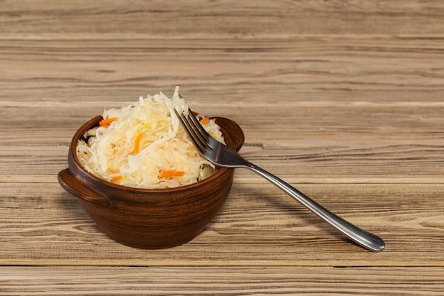 Schüssel sauerkraut mit karotten auf holzuntergrund mariniertes gemüse vegetarisches essen