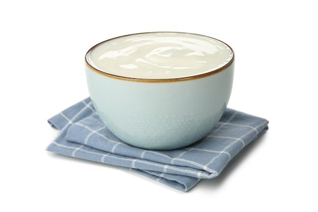 Schüssel sauerrahmjoghurt und serviette lokalisiert auf weiß