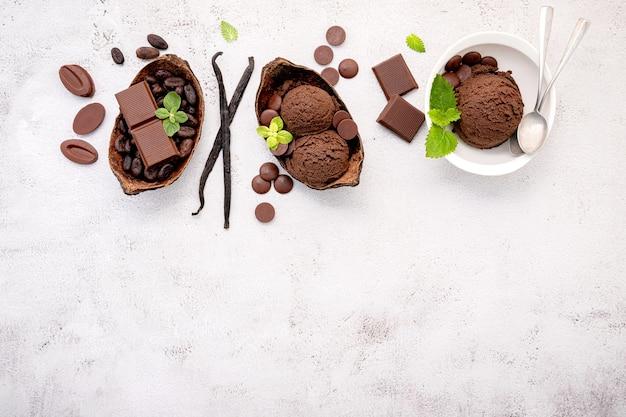 Schüssel schokoladeneisaromen mit dunkler schokolade oben auf weißem betonhintergrund