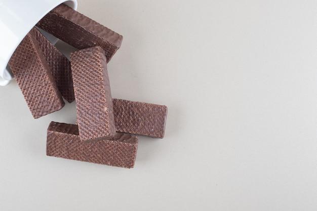 Schüssel schokoladenwaffeln verschüttete auf marmorhintergrund.