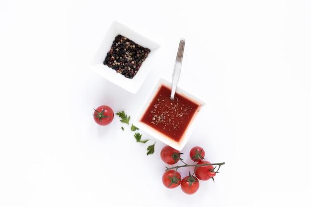 Schüssel schwarzer pfeffer und tomatensauce lokalisiert auf weißer oberfläche