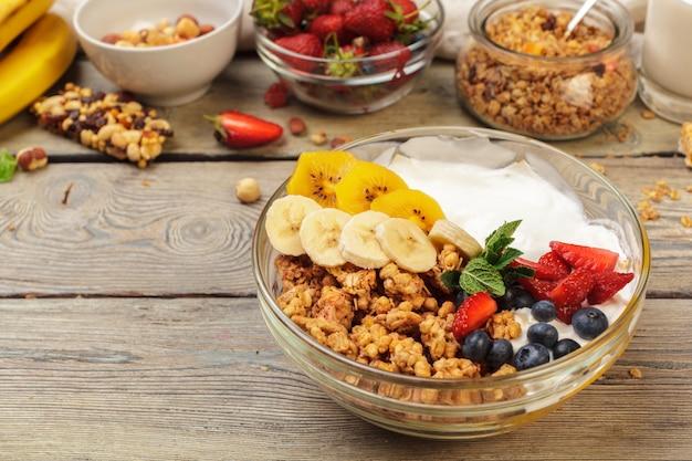 Schüssel selbst gemachtes granola mit joghurt und frischen beeren auf hölzernem
