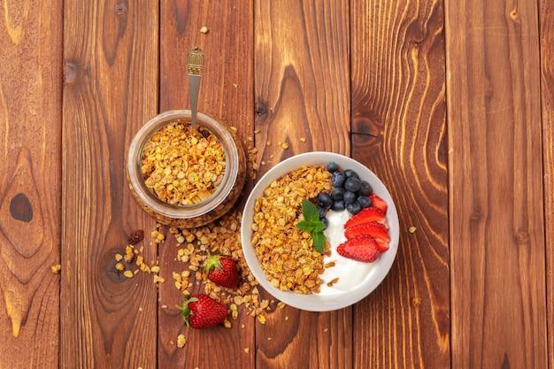 Schüssel selbst gemachtes granola mit joghurt und frischen beeren auf holz