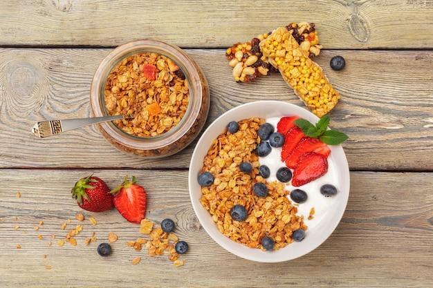 Schüssel selbst gemachtes granola mit joghurt und frischen beeren auf holzoberfläche