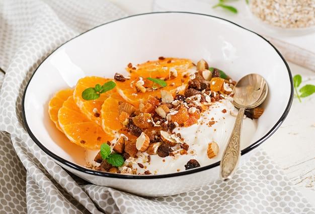 Schüssel selbst gemachtes granola mit jogurt und tangerine auf weißem holztisch. fitness essen.