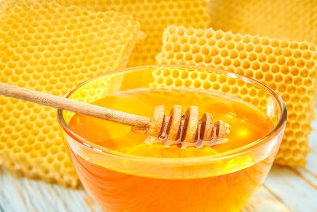 Schüssel süßer honig auf blauem rustikalem tisch, mit wabe, nahaufnahme.