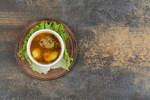 Schüssel suppe mit fleischbällchen auf holzbrett.