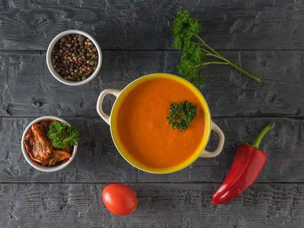 Schüssel suppenpüree von paprika und sellerie auf einem holztisch. suppe der vegetarischen ernährung. flach liegen. der blick von oben.