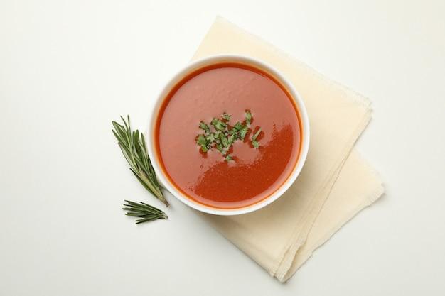 Schüssel tomatensuppe und handtuch auf weiß