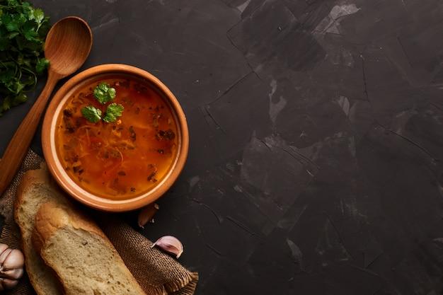Schüssel traditionelle suppe borscht auf schwarzem tisch. flach liegen. speicherplatz kopieren.