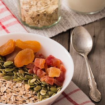 Schüssel trockene früchte, kürbiskerne und hafer blättert auf frühstückstisch ab