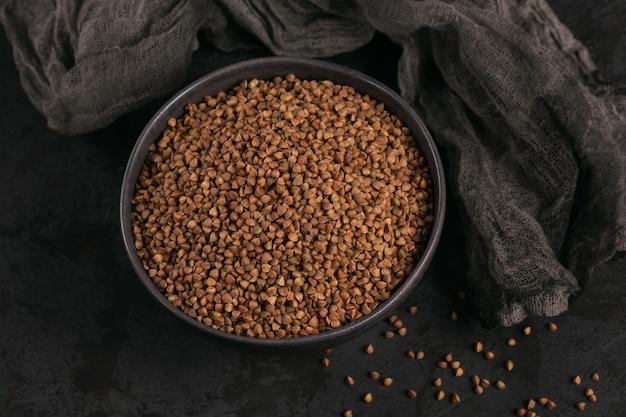 Schüssel trockene rohe buchweizengrütze auf einem dunklen hintergrund. buchweizenbrei-konzept kochen.