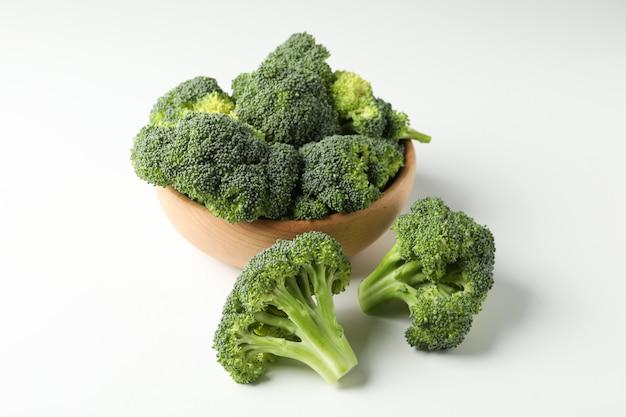 Schüssel und brokkoli auf weißer oberfläche. frisches gemüse