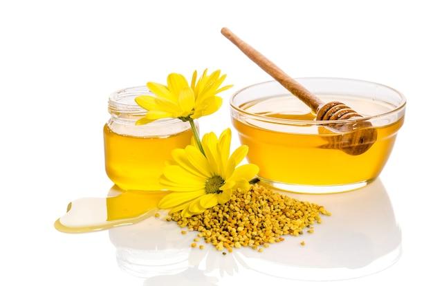 Schüssel und das glas honig in der nähe eines haufens von pollen und blumen isoliert auf weiß