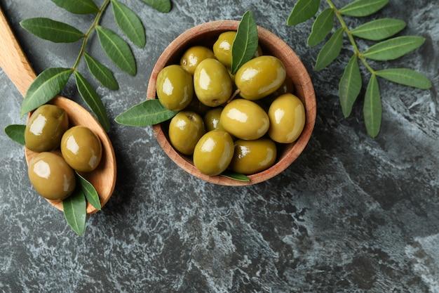 Schüssel und löffel oliven und blätter auf schwarzem rauchigem hintergrund