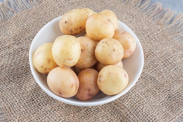 Schüssel voll gekochter kartoffel auf sack.